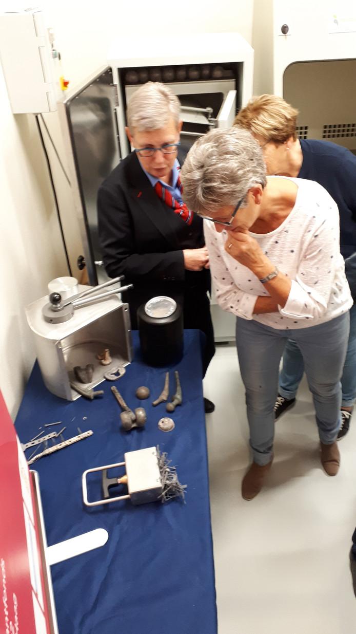 Bezoekers krijgen uitleg over wat er met metalen implantaten als kunstknieen en kunstheupen gebeurt na de crematie.