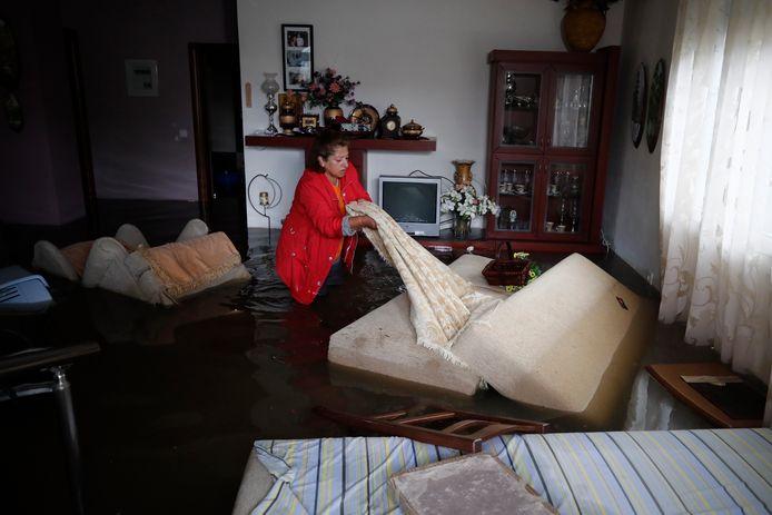 Een bewoonster van Kavalari probeert huisraad te redden uit haar overstroomde woning.