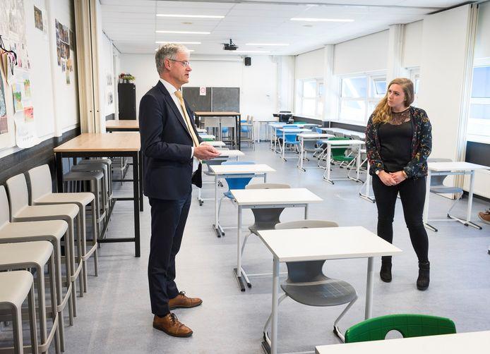 Onderwijsminister Arie Slob laat zich voorlichten door een docente in een leeg eindexamenlokaal van het Niftarlake College.
