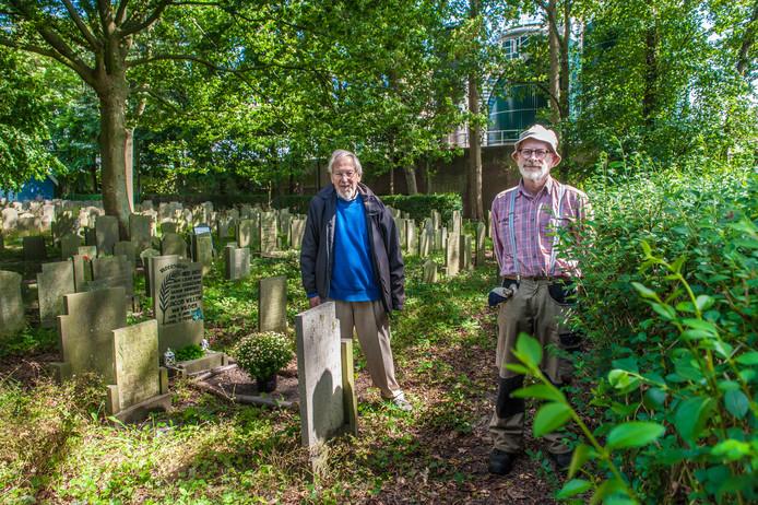 William Bik (links) en Koos Massar bij de ligusterhaag waaronder 56 Gouwenaars anoniem liggen begraven. Ze willen hier graag een plaquette met de namen van de doden bij plaatsen.