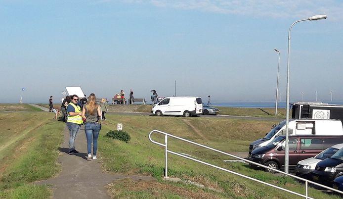 Voordat er daadwerkelijk gefilmd gaat worden wachten Linda de Mol en de andere actrices in de verte al op een bankje aan de Oosterschelde.