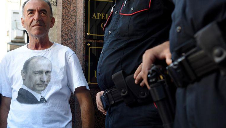 Een man in een shirt met de Russische president Vladimir Poetin staat voor de ingang van de rechtszaal in Podgorica, op de eerste dag van het proces. Beeld ap