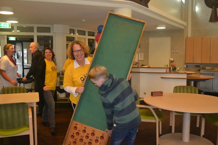 Juffrouw Marijke krijgt hulp bij het klaarzetten van het Barakspel.