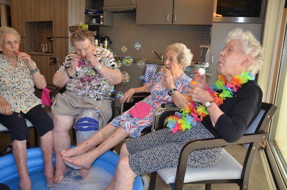 De bewoonsters van Hof Ter Engelen genieten van hun ijsje terwijl ze pootjebaden.