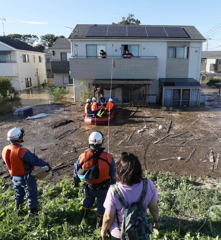 Brandweerlieden in de stad Kawagoe zijn bezig inwoners te evacueren van het balkon van hun onder water gestroomde huis na het overtrekken van de tyfoon Hagibis.  Beeld null