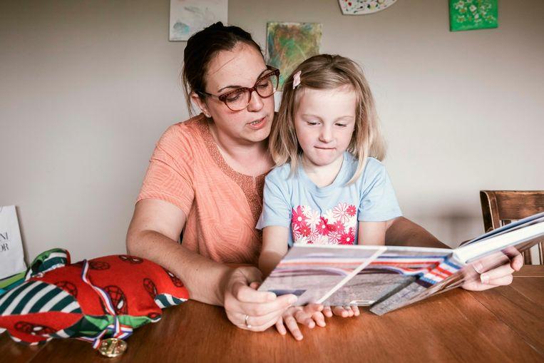 Inge bekijkt samen met haar dochtertje het fotoboek van Sam.