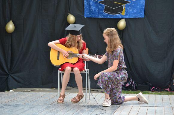 Deze leerlinge toont wat ze kan met haar gitaar.