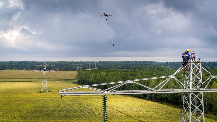 Met een drone wordt een draad tussen twee hoogspanningsmasten getrokken.