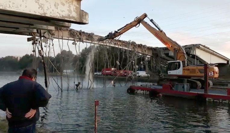 De brug wordt met een kraan afgebroken.