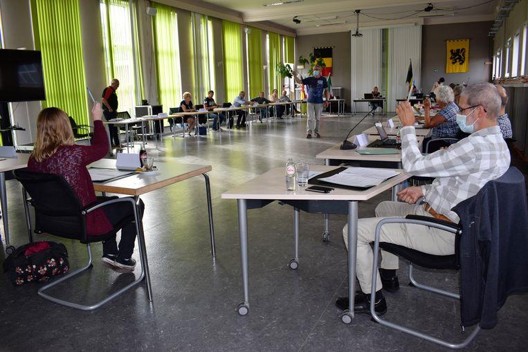 De eerste Zelzaatse gemeenteraad na de coronacrisis: een gigantisch lange tafel en iedereen zijn eigen balpen.