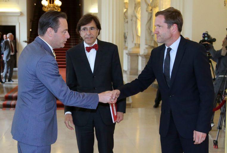 N-VA-voorzitter Bart De Wever schudt de hand van huidig PS-voorzitter Paul Magnette in aanwezigheid van Elio Di Rupo, hier bij de regeringsvorming van 2014. Vandaag zit het er opnieuw bovenarms op tussen beide partijen.