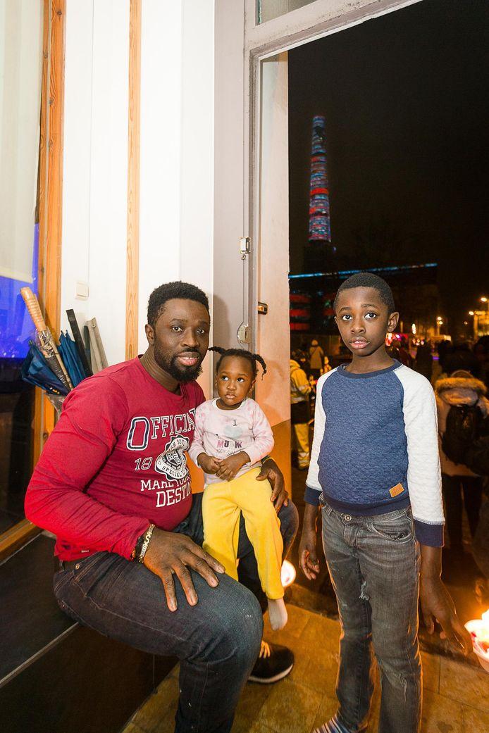 Charles Asamiah en zijn kinderen Tyrese en Leah met zicht op de metershoge schoorsteen van de atoomcentrale.