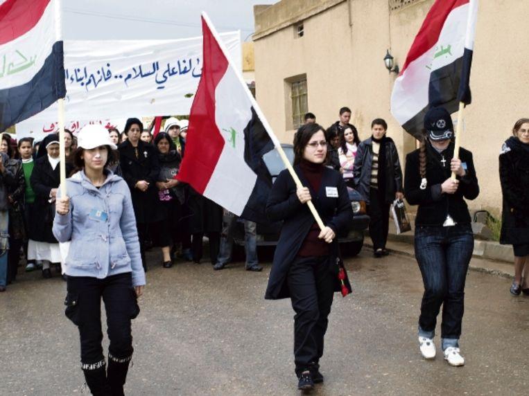 Christenen in Al Qosh dragen spandoeken met leuzen die om vrede vragen, en Iraakse vlaggen. (FOTO JUDIT NEURINK) Beeld