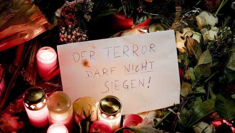 Kaarsen en bloemen in de buurt van de plek waar een vrachtwagen afgelopen maandagavond inreed op een kerstmarkt in Berlijn. Daarbij vielen 12 doden en 49 gewonden, van wie een aantal nog in ziekenhuizen ligt. Beeld ANP