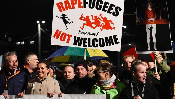 Demonstranten van Pegida in Leipzig dragen een bord waarop staat: Raperefugees not welcome - 'verkrachtvluchtelingen niet welkom'.