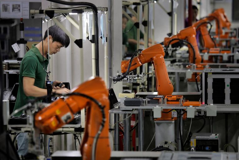 Fabrieksarbeider aan het werk tussen oranje robot-armen, in een fabriek in Shenzhen, China. Beeld null
