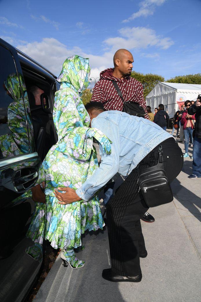 Echt praktisch was de outfit van Cardi niet, ze moet door twee assistenten uit de wagen geholpen worden.