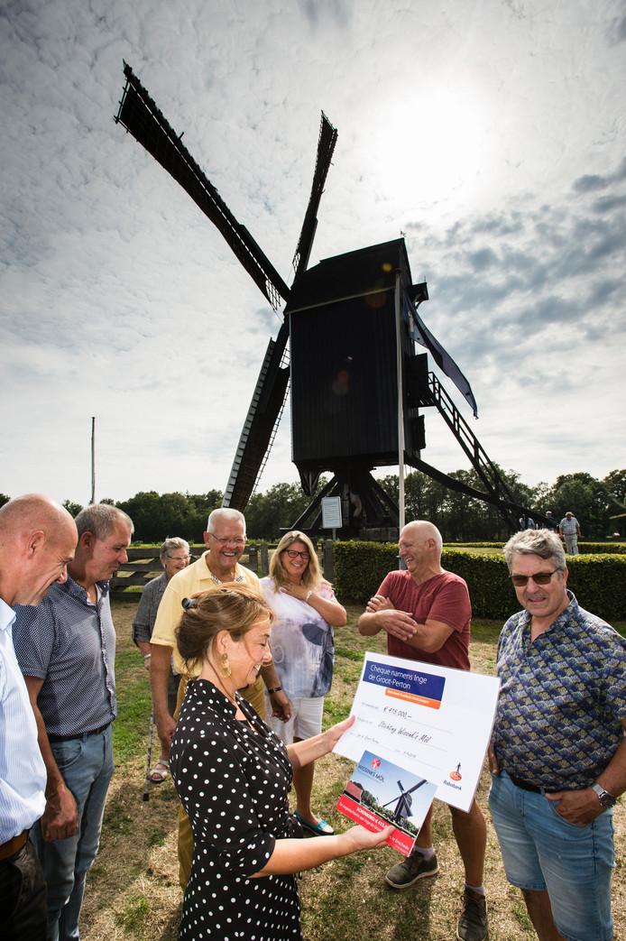 Evelien Biermans, secretaris van de stichting Wissinks Möl, ontvangt uit handen van  Rob Schenk (gele polo), executeur-testamentair van de nalatenschap van schilder/tekenaar Jacq de Groot, een cheque ter waarde van 415.000 euro.