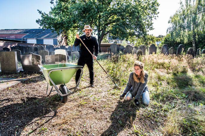 Joke Niekamp en Pierre Vallée pakken de begraafplaats aan. Rechts het stuk dat nog gedaan moet worden.