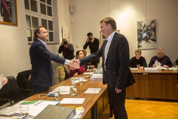 Damien Thiéry (links) en Yves Ghequiere schudden mekaar de hand nadat die laatste de eed aflegt op de installatievergadering in Linkebeek. Maar achter de schermen wordt het spel hard gespeeld.