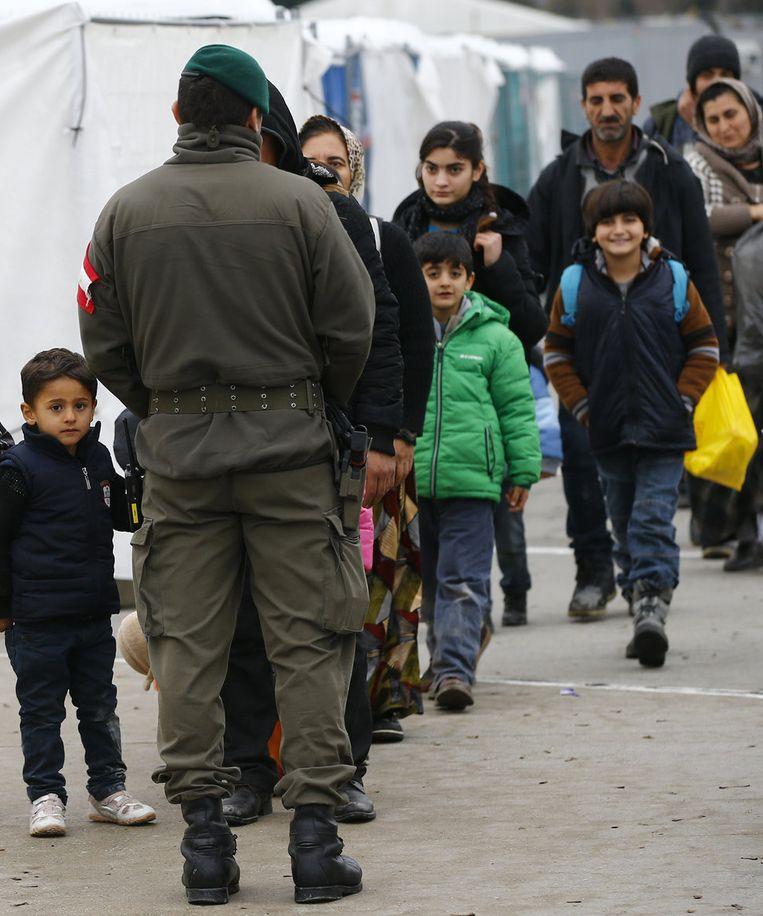 Een Oostenrijkse militair kijkt naar migranten die de grens oversteken tussen Slovenië en Oostenrijk. Beeld reuters