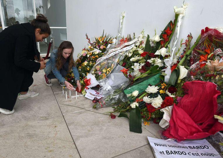 Toeristen leggen bloemen neer bij het Bardomuseum. Beeld null