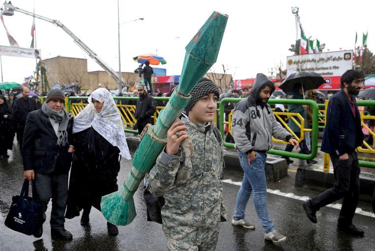 Een Iraanse tiener draagt een namaakraketwerper.    Beeld AP