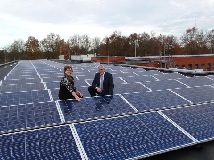De Twenterandse wethouders Martha van Abbema en Ben Engberts poseren trots tussen de zonnepanelen op het dak van het Twenterandse gemeentehuis in Vriezenveen.