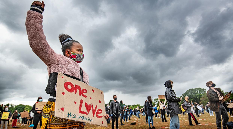 Een meisje in roze jas met protestbord 'One love' is een van de demonstranten vrijdag in Nijmegen tegen racisme. Beeld Guus Dubbelman / de Volkskrant