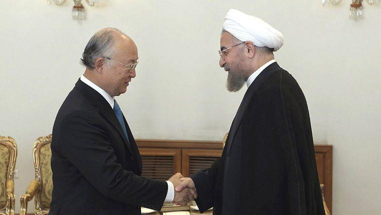 Yukiya Amano, hoofd van het Internationaal Agentschap voor Atoomenergie, schudt de hand van de Iraanse president Hasan Rouhani. Beeld ap