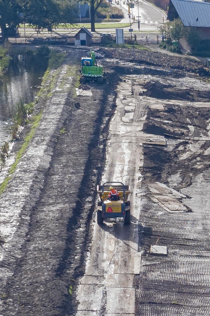 Werkzaamheden aan de dijk bij het Zwarte Pad in Boskoop, dat nu wordt opgehoogd.