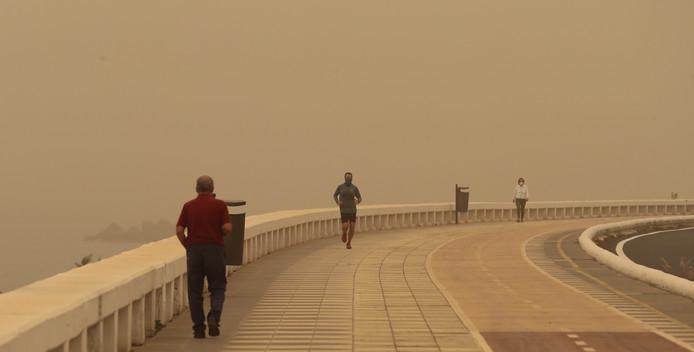 Mensen trotseren de zandstorm en maken een wandelingetje langs de promenade.