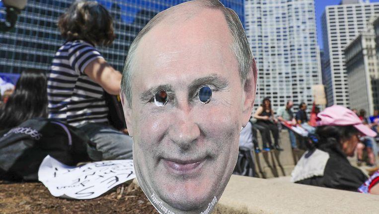 Demonstranten met een Poetin-masker bij de Trump-toren in Chicago. Beeld epa