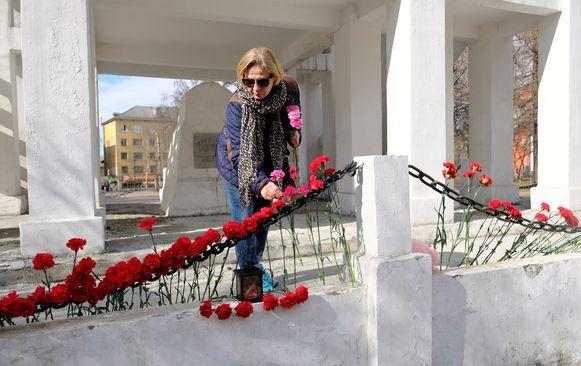 Een vrouw plaatst bloemen bij een monumentje voor de slachtoffers.