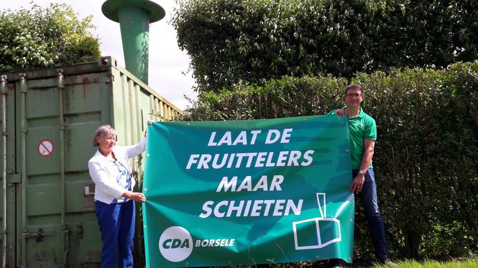 Marga van de Plasse en Peter van 't Westeinde van het CDA tonen een spandoek met een steunbetuiging voor Borselse fruittelers. Op de achtergrond een hagelkanon in een boomgaard.
