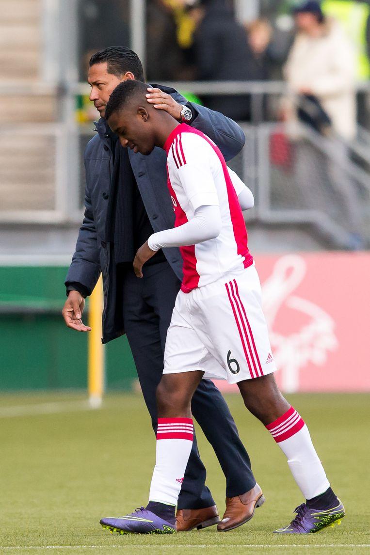 Riechedly Bazoer van Ajax krijgt na het duel steun van trainer Henk Fraser van ADO Den Haag. Beeld pro shots