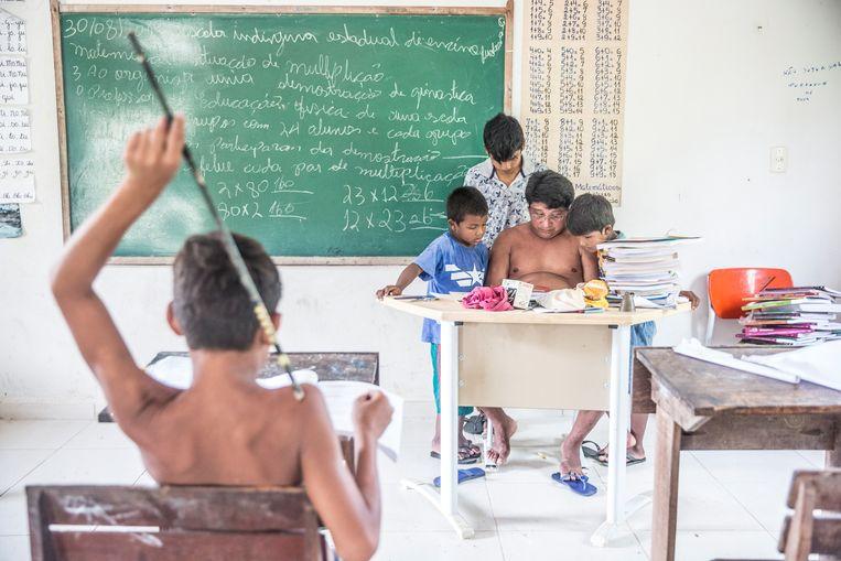 Leraar Batiti Karipuna geeft les. Of ja, hij bekijkt een filmpje op zijn gsm en les is eigenlijk ook best snel klaar omdat het gewoon te heet is, zegt hij. Beeld Marlena Waldthausen
