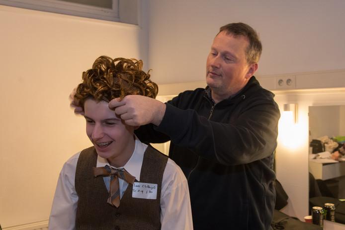 Regisseur Jacco van Lunteren kleedt een van de acteurs aan.