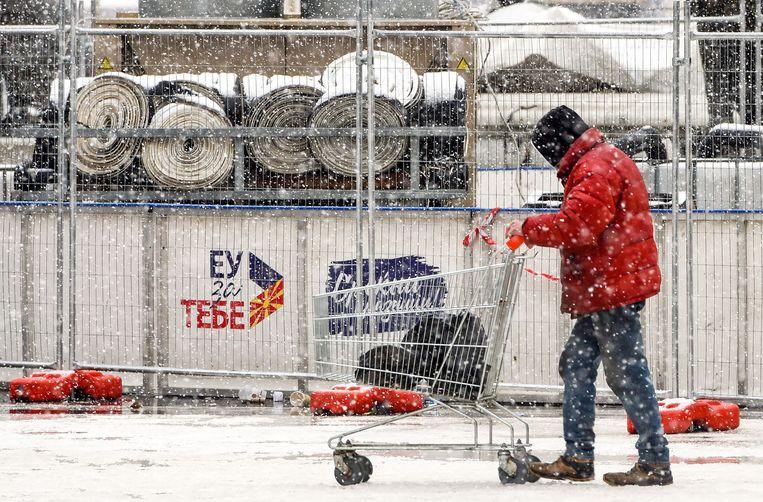 Een man duwt zijn winkelwagentje door Skopje, de hoofdstad van wat voortaan Noord-Macedonië heet. Beeld AFP