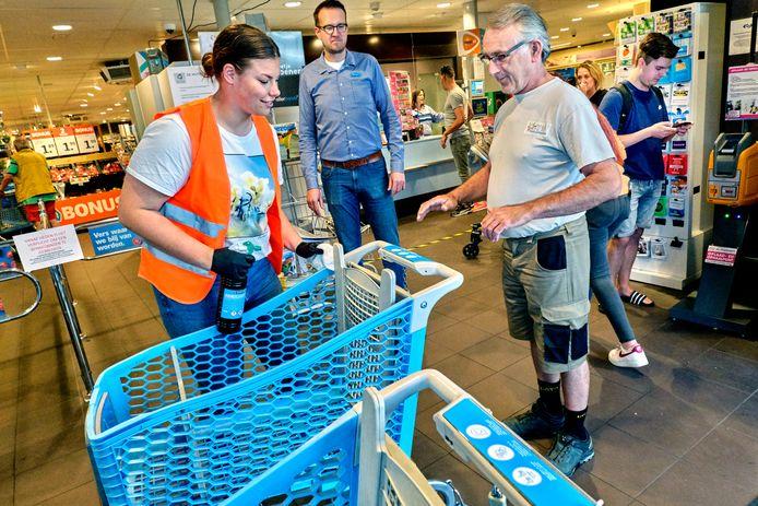 Medewerkers die de karretjes schoonmaken worden regelmatig uitgescholden. Op de achtergrond staat AH-bedrijfsleider Wouter van der Heiden.