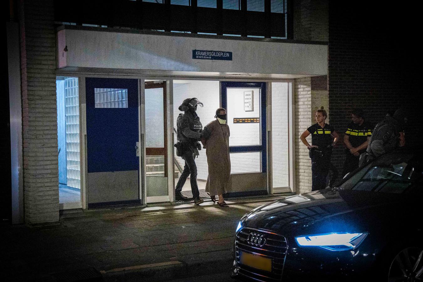 De aangehouden man wordt met een kap over zijn hoofd naar buiten gebracht  in Arnhem.