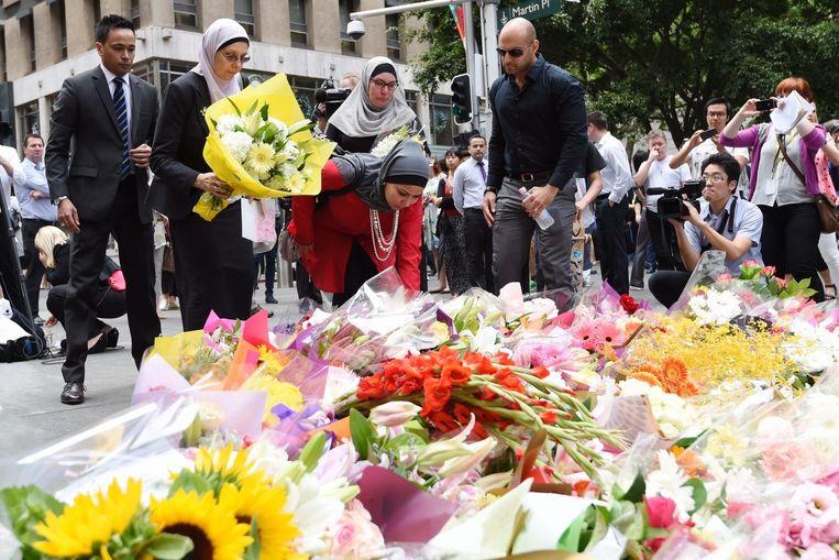 Bloemen worden neergelegd in het centrum van Sydney. Beeld null