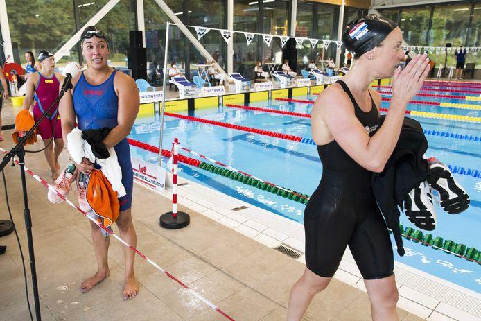 Ranomi Kromowidjojo staat de pers te woord na haar 100 meter vrije slag terwijl Femke Heemskerk voorbij loopt tijdens de Long Course Challenge.