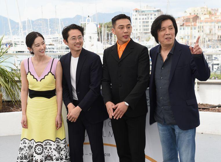 Regisseur Lee Chang-dong (r) met drie acteurs uit zijn film Burning. Beeld Getty Images