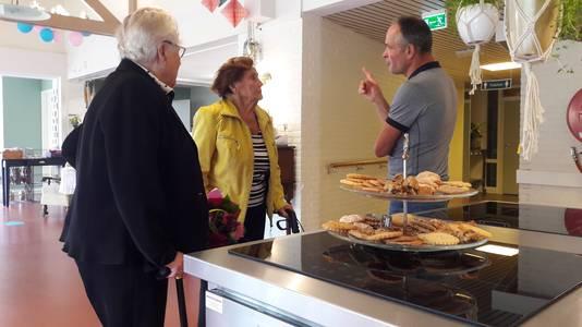 Bakker Jos Veltmaat geeft uitleg aan twee bezoekers van de opening.