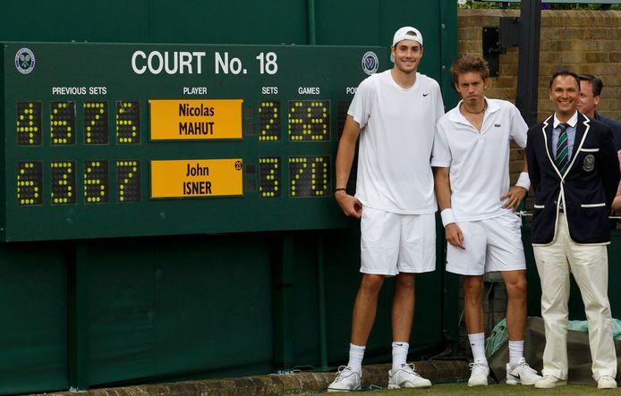 John Isner en Nicolas Mahut poseren bij het scorebord.