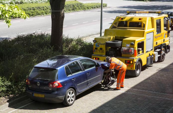 De Wegenwacht sleept een auto naar een garage.