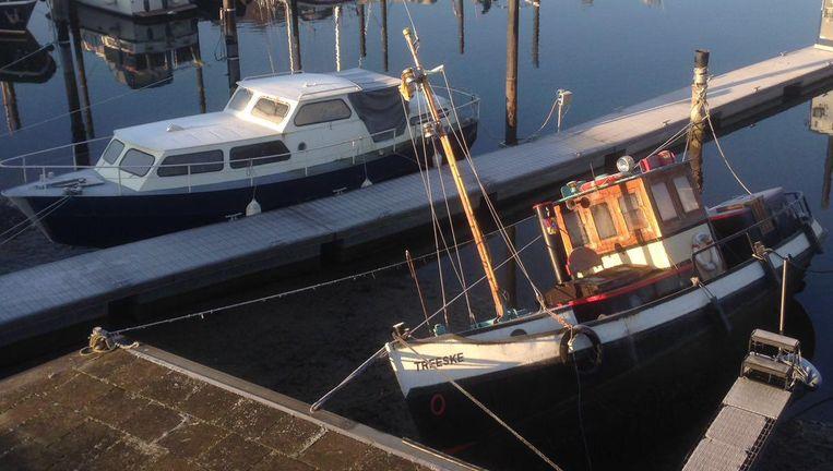 Boot ligt scheef in jachthaven Grave door gezakt waterpeil in de Maas. Beeld Peter de Graaf
