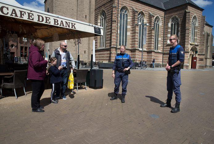 Handhavers Christiane van Diermen en Ruben Holdijk manen een gezin om niet op het terras te gaan zitten.