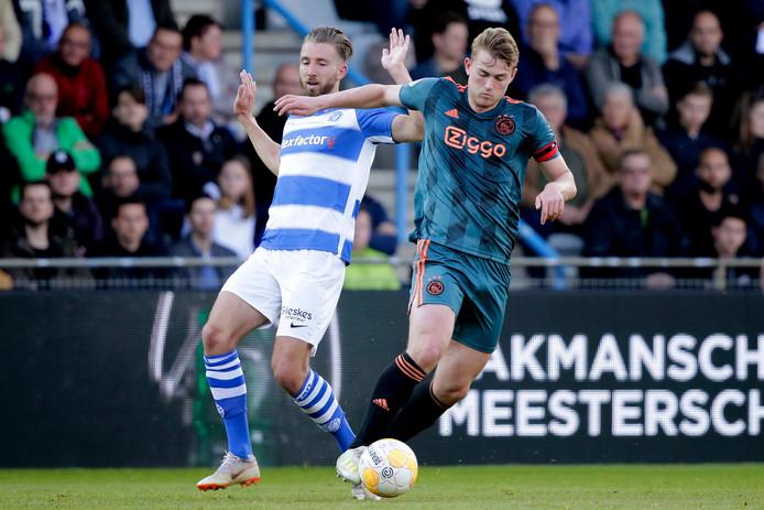 Ajax-aanvoerder Matthijs de Ligt schudt Fabian Serrarens van De Graafschap af.
